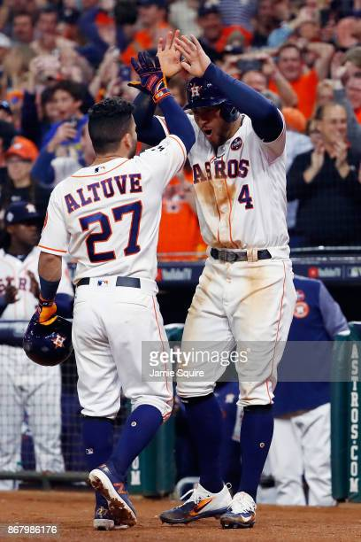 Jose Altuve of the Houston Astros celebrates with George Springer after hitting a threerun home run during the fifth inning against the Los Angeles...