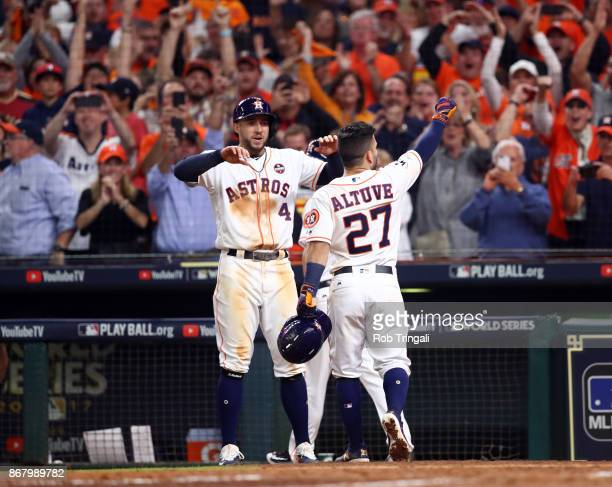 Jose Altuve of the Houston Astros celebrates with George Springer after hitting a threerun home run in the fifth inning of Game 5 of the 2017 World...
