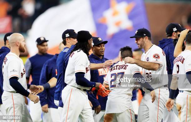 Jose Altuve of the Houston Astros celebrates with Justin Verlander and teammates after scoring the winning run in their 21 win over the New York...