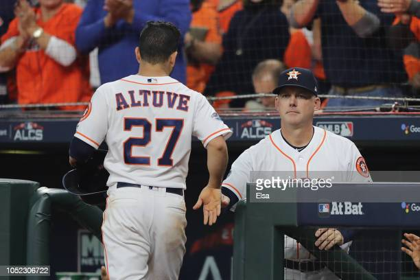 Jose Altuve of the Houston Astros celebrates with manager AJ Hinch after scoring a run in the first inning against the Boston Red Sox during Game...