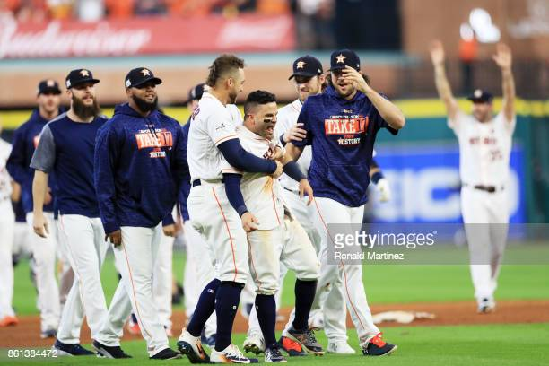 Jose Altuve of the Houston Astros celebrates with teammates after scoring the winning run in their 21 win over the New York Yankees during game two...