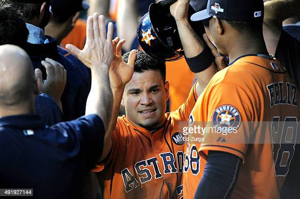 Jose Altuve of the Houston Astros celebrates with teammates in the dugout after scoring a run in the first inning during game one of the American...