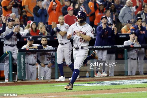 Jose Altuve of the Houston Astros comes home to score a run on a single by Michael Brantley against the Washington Nationals during the fifth inning...