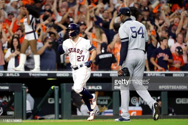 Jose Altuve of the Houston Astros comes home to score following his ninth inning walkoff tworun home run as Aroldis Chapman of the New York Yankees...