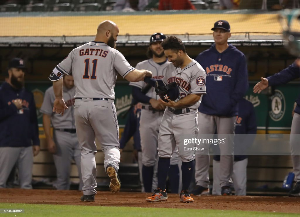 Jose Altuve #27 of the Houston Astros congratulates Evan Gattis #11 after he hit a solo home run in the seventh inning against the Oakland Athletics at Oakland Alameda Coliseum on June 13, 2018 in Oakland, California.