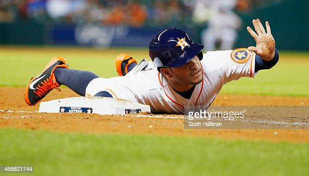Jose Altuve of the Houston Astros dives abck into first base during the fourth inning against the Cleveland Indians during their game at Minute Maid...