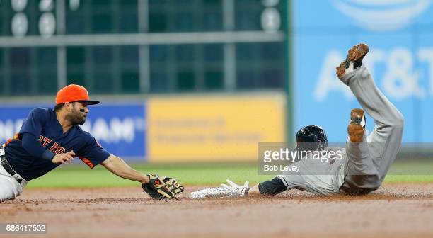 Jose Altuve of the Houston Astros dives but unable to beat Yan Gomes of the Cleveland Indians to the base in the second inning at Minute Maid Park on...