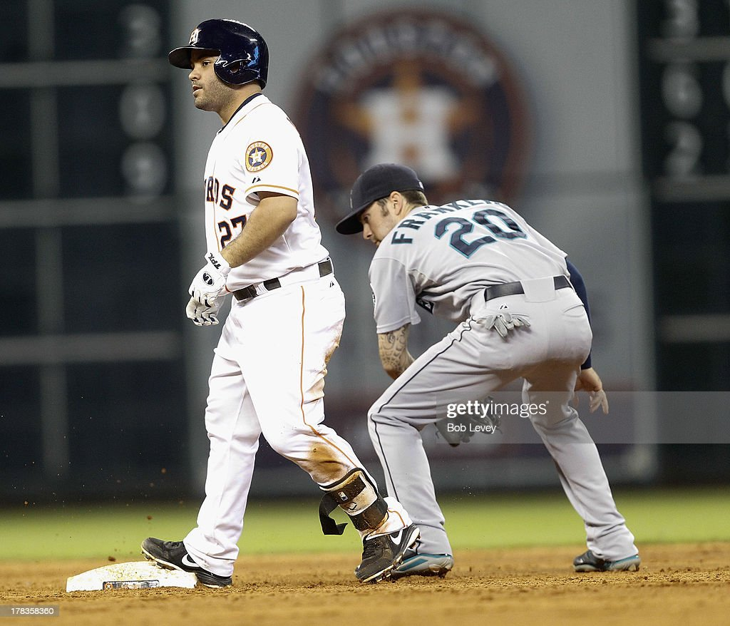 Jose Altuve #27 of the Houston Astros doubles in the sixth inning as Nick Franklin #20 of the Seattle Mariners is late with the tag at Minute Maid Park on August 29, 2013 in Houston, Texas.