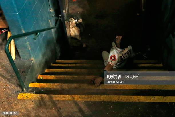 Jose Altuve of the Houston Astros falls down stairs in the dugout after defeating the Los Angeles Dodgers in game five of the 2017 World Series at...