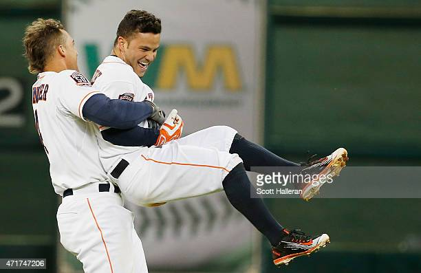 Jose Altuve of the Houston Astros gets a hug from George Springer after Aluve's tenth inning game-winning RBI single to defeat the Seattle Mariners...