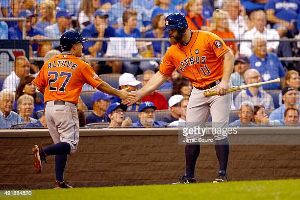 Jose Altuve of the Houston Astros high fives Evan Gattis of the Houston Astros after scoring a run in the first inning during game one of the...