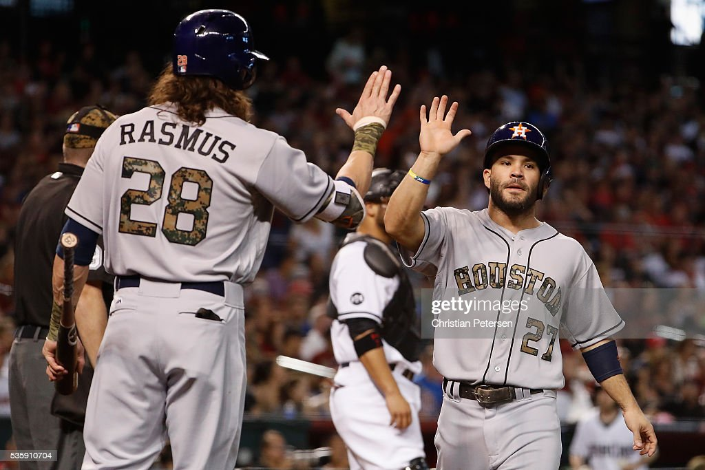 Jose Altuve #27 of the Houston Astros high-fives Colby Rasmus #28 after scoring a run against the Arizona Diamondbacks during the fourth inning of the MLB game at Chase Field on May 30, 2016 in Phoenix, Arizona.
