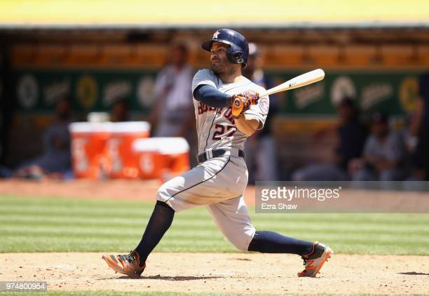 Jose Altuve of the Houston Astros hits a double that scores a run in the sixth inning against the Oakland Athletics at Oakland Alameda Coliseum on...
