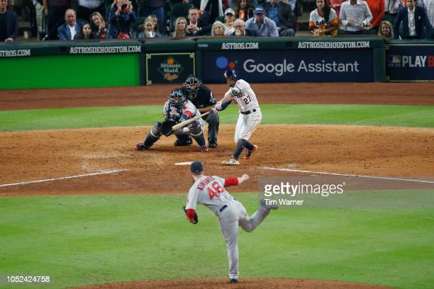 Jose Altuve of the Houston Astros hits a sacrifice RBI in the eighth inning against the Boston Red Sox during Game Four of the American League...