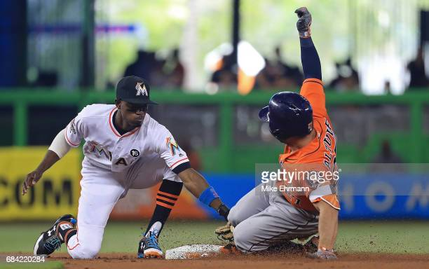 Jose Altuve of the Houston Astros hits an RBI double after sliding under the tag from Dee Gordon of the Miami Marlins during a game at Marlins Park...