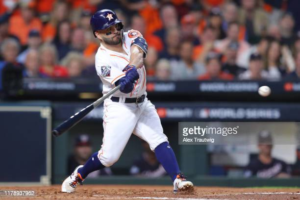 Jose Altuve of the Houston Astros hits an RBI sacrifice fly in the first inning during Game 6 of the 2019 World Series between the Washington...