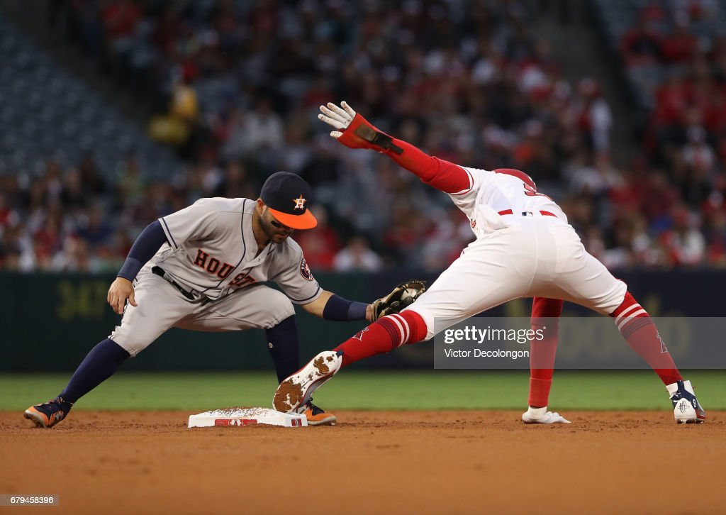 Jose Altuve #27 of the Houston Astros holds the tag on Cameron Maybin #9 of the Los Angeles Angels of Anaheim on the steal attempt at second base during the first inning of the MLB game at Angel Stadium of Anaheim on May 5, 2017 in Anaheim, California. Maybin was originally called safe but upon review the call was overturned and Maybin was ruled out at second base.