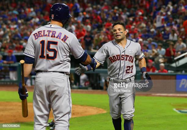 Jose Altuve of the Houston Astros is congratulated by Carlos Beltran for hitting a solo home run in the ninth inning at Globe Life Park in Arlington...