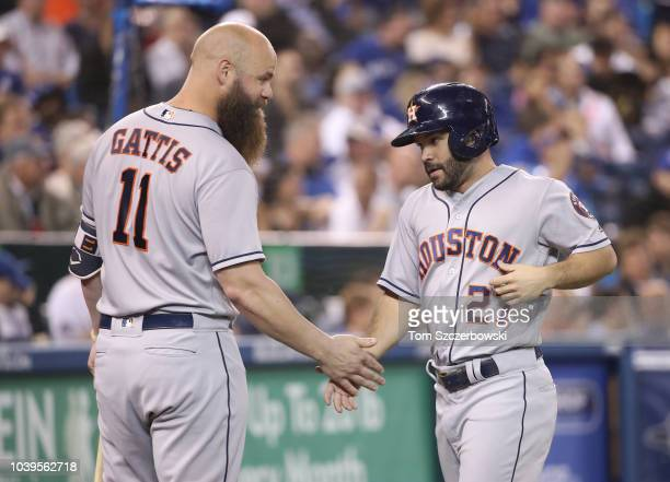 Jose Altuve of the Houston Astros is congratulated by Evan Gattis after scoring a run in the third inning during MLB game action against the Toronto...