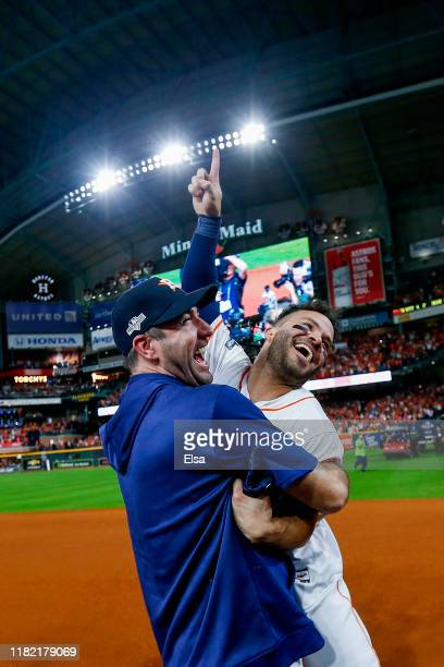 Jose Altuve of the Houston Astros is congratulated by his teammate Justin Verlander following his ninth inning walk-off two-run home run to defeat...