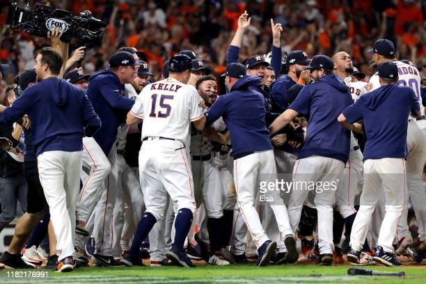 Jose Altuve of the Houston Astros is congratulated by his teammates following his ninth inning walk-off two-run home run to defeat the New York...