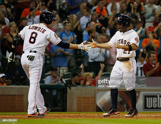 Jose Altuve of the Houston Astros is greeted by Jed Lowrie after Altuve scored a run in the eighth inning during their game against the Tampa Bay...