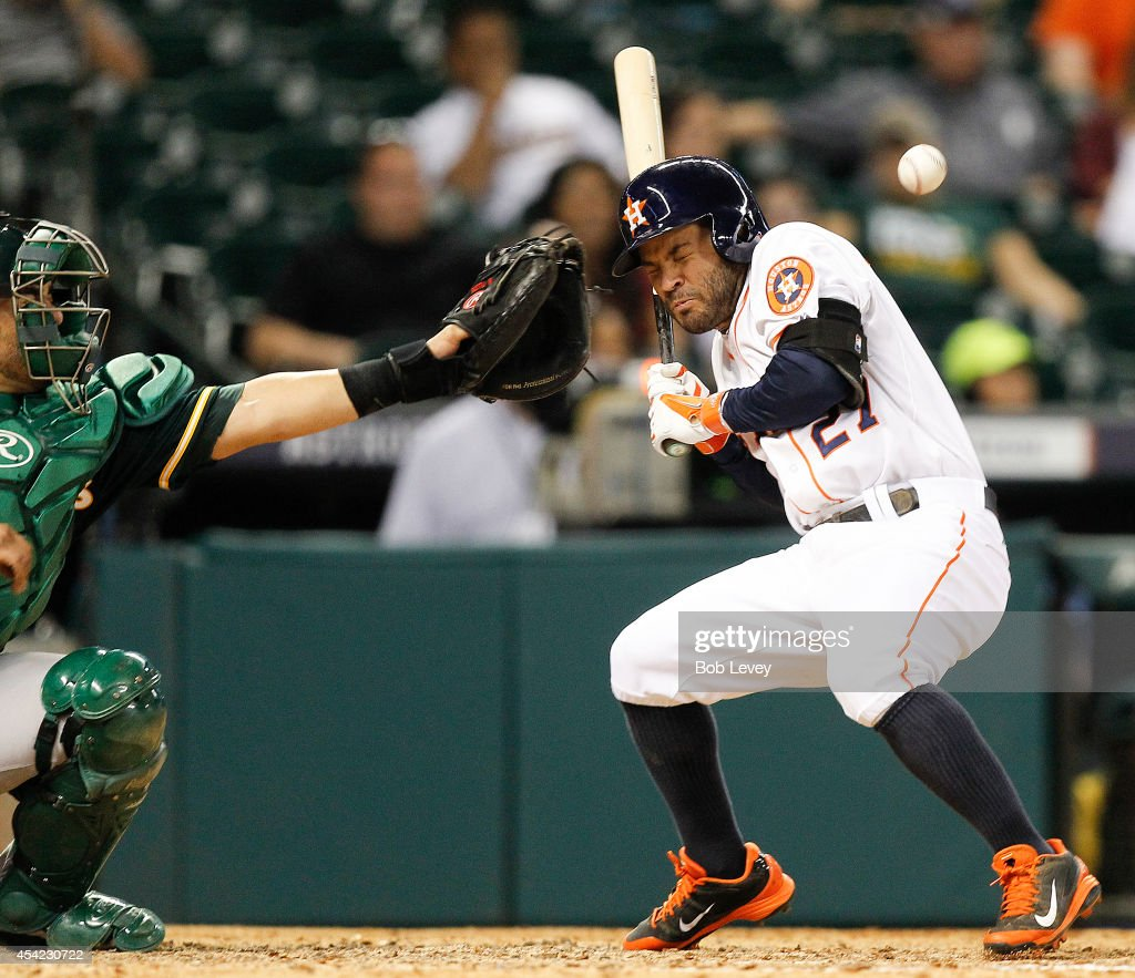 Jose Altuve #27 of the Houston Astros is hit by a pitch in the eighth inning against the Oakland Athletics at Minute Maid Park on August 26, 2014 in Houston, Texas.