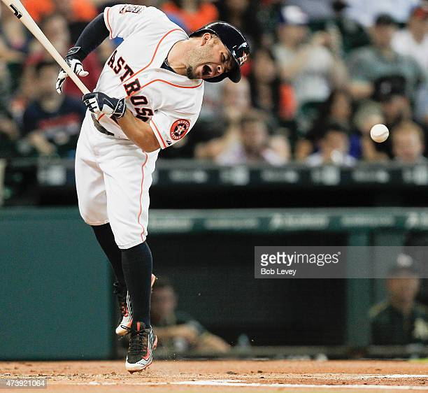 Jose Altuve of the Houston Astros is hit by a pitch in the first inning against the Oakland Athletics at Minute Maid Park on May 18 2015 in Houston...