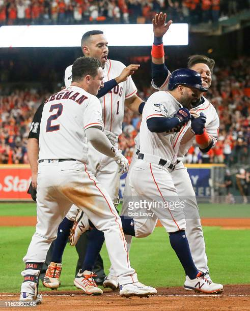 Jose Altuve of the Houston Astros is mobbed by Alex Bregman, Carlos Correa and Yuli Gurriel as he approaches home plate after hitting a walk-off home...