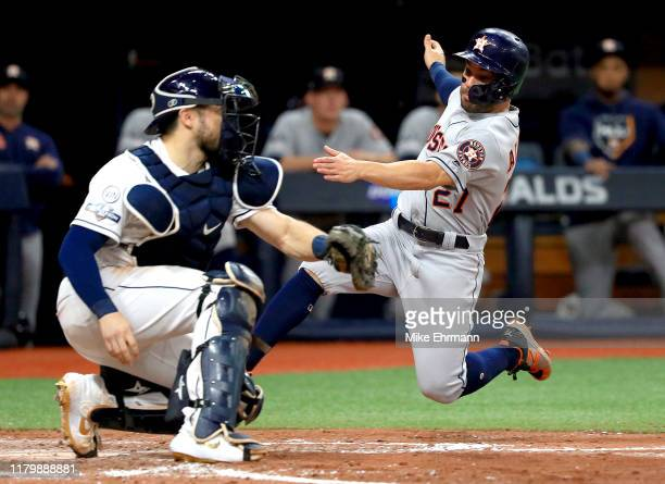 Jose Altuve of the Houston Astros is tagged out at home plate by Travis d'Arnaud of the Tampa Bay Rays while attempting to score a run during the...