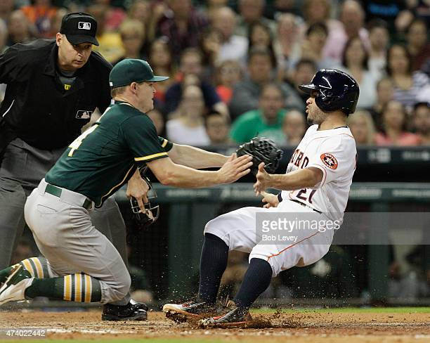 Jose Altuve of the Houston Astros is tagged out by Sonny Gray of the Oakland Athletics trying to score as home plate umpire Andy Fletcher looks on in...