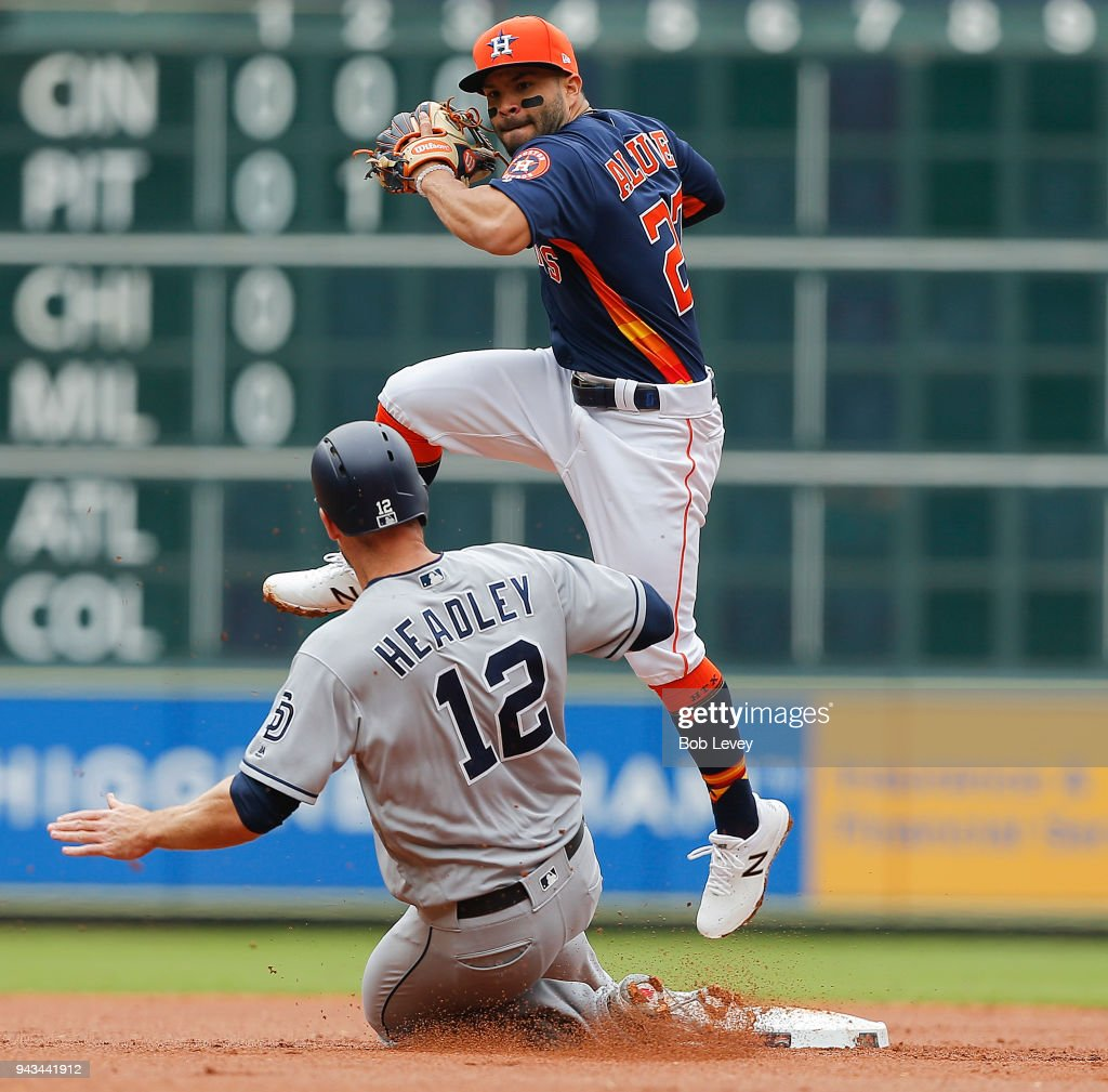 Jose Altuve #27 of the Houston Astros leaps to avoid the slide by Chase Headley #12 of the San Diego Padres is forced out in the second inning at Minute Maid Park on April 8, 2018 in Houston, Texas.