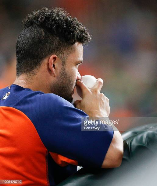 Jose Altuve of the Houston Astros looks on from the dugout against the Texas Rangers at Minute Maid Park on July 27 2018 in Houston Texas Altuve...