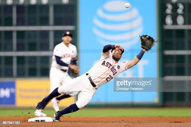 Jose Altuve of the Houston Astros reaches for a ball as he attempts to tag out Logan Forsythe of the Los Angeles Dodgers during the first inning in...