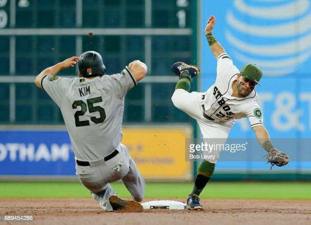 Jose Altuve of the Houston Astros reaches for the ball as Hyun Soo Kim of the Baltimore Orioles slides into second base in the second inning at...