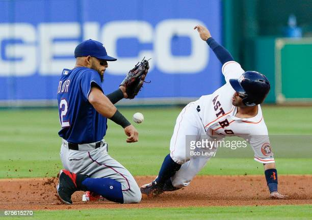 Jose Altuve of the Houston Astros reaches second base after an error by left fielder Nomar Mazara as Rougned Odor is unable to handle the throw in...