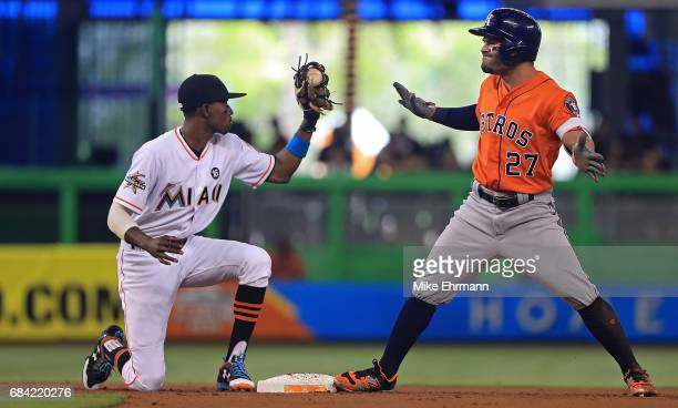 Jose Altuve of the Houston Astros reacts to an RBI double after sliding under the tag from Dee Gordon of the Miami Marlins during a game at Marlins...