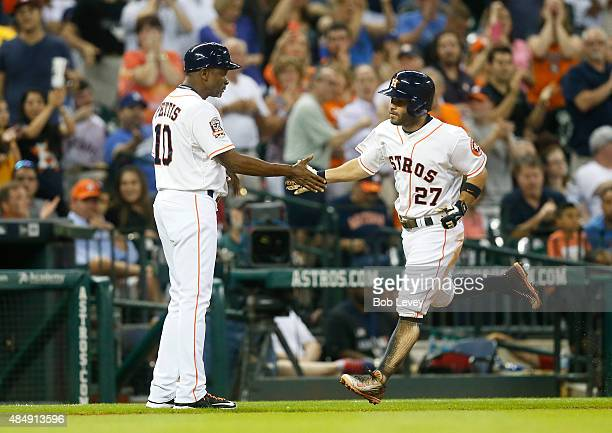 Jose Altuve of the Houston Astros receives congratulations from third base coach Gary Pettis after hitting a home run in the sixth inning against the...