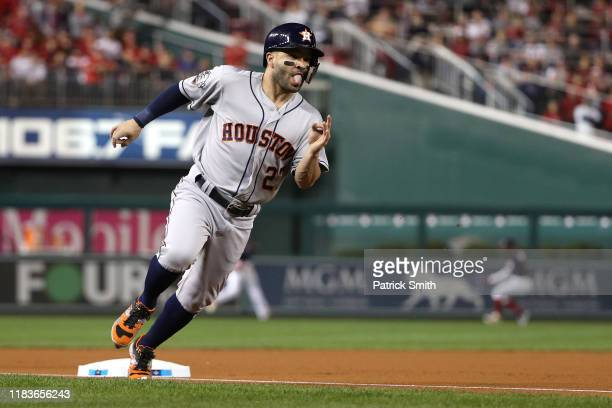 Jose Altuve of the Houston Astros rounds third base and scores a run on a hit by Alex Bregman against the Washington Nationals during the first...