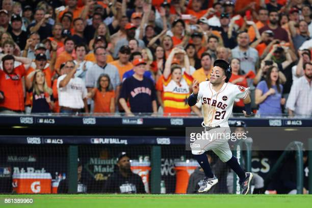 Jose Altuve of the Houston Astros runs home to score the winning run against the New York Yankees in the ninth inning during game two of the American...
