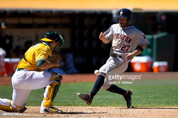 Jose Altuve of the Houston Astros scores a run past Josh Phegley of the Oakland Athletics during the sixth inning at Oco Coliseum on August 9 2015 in...