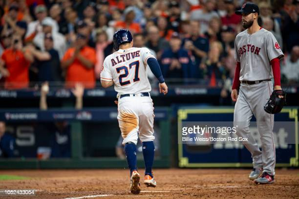 Jose Altuve of the Houston Astros scores as Rick Porcello of the Boston Red Sox looks on during the fourth inning of game four of the American League...