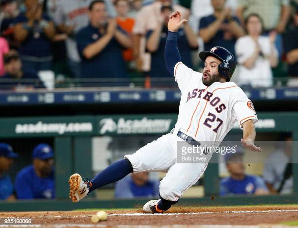 Jose Altuve of the Houston Astros scores on a double by Evan Gattis in the first inning against the Toronto Blue Jays at Minute Maid Park on June 27...
