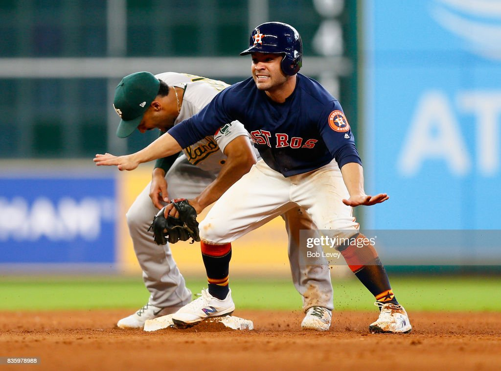 Jose Altuve #27 of the Houston Astros signals safe as he steals second base in the eighth inning as Marcus Semien #10 of the Oakland Athletics is late on the tag at Minute Maid Park on August 20, 2017 in Houston, Texas.