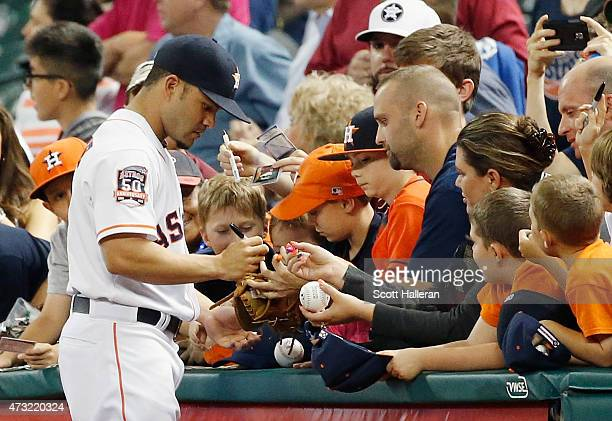 Jose Altuve of the Houston Astros signs autographs for fans before the start of their game against the San Francisco Giants at Minute Maid Park on...