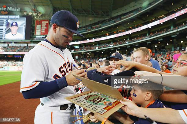 Jose Altuve of the Houston Astros signs autographs for fans before the start of their game against the Los Angeles Angels of Anaheim at Minute Maid...