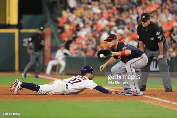 Jose Altuve of the Houston Astros slides back to first base safely against Ryan Zimmerman of the Washington Nationals during the fifth inning in Game...