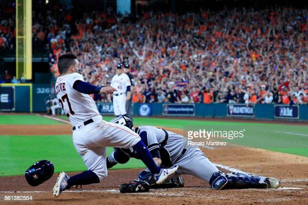 Jose Altuve of the Houston Astros slides home to score the winning run against Gary Sanchez of the New York Yankees in the ninth inning during game...