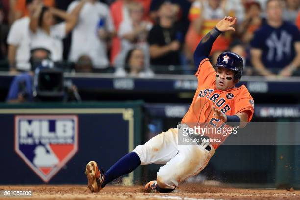 Jose Altuve of the Houston Astros slides into home to score on a single by Carlos Correa in the fourth inning against the New York Yankees during...