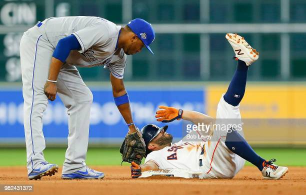 Jose Altuve of the Houston Astros slides into second base for a double ahead of the tag by Alcides Escobar of the Kansas City Royals in the fourth...
